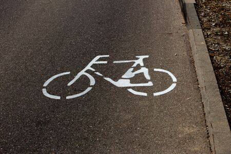 Bicycle lane symbol painted on a road next to a curb