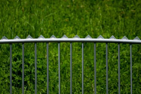 Modern metal fence with triangle spikes on the top and grass in the background