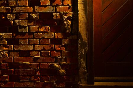 Old grungy and damaged red brick wall at night beside a wooden door with light of a lantern shining on it