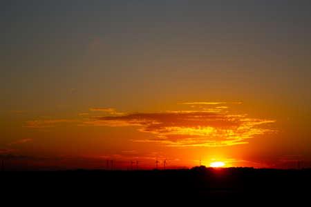 Sunrise with silhouettes of wind turbines on the horizon Archivio Fotografico