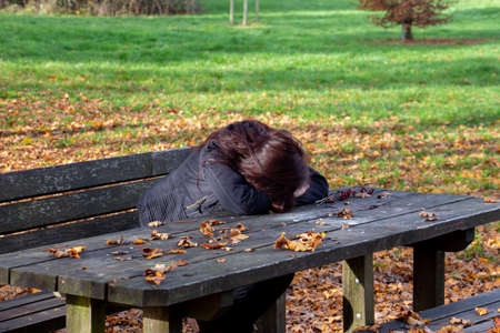 Woman with dark hair sitting at a picnic table with her head down on her hands. Autumn leaves laying everywhere around.