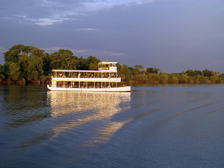 It is sunset time and a boat with tourists on board make a trip over the zambezi river on this romantic evening.