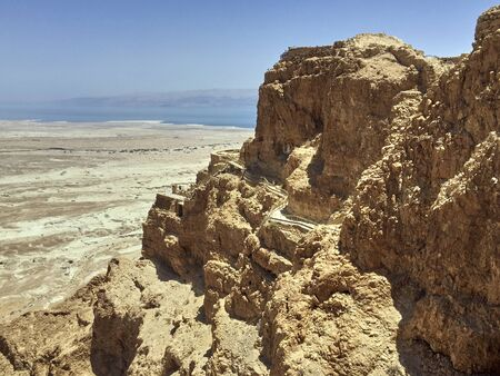 A view over the Israeli desert in front of the rock fortress Masada. In the background you can see the Dead Sea