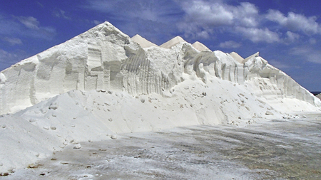 White salt on a mountain buried in a sea on the Spanish Mediterranean island of Majorca, in front of a blue cloudy sky Stock Photo