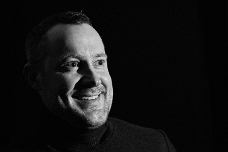 A young 30 to 45 year old man looks smiling, it looks as if he is the man of an interview, black and white portrait photo on a black background