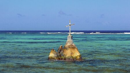 A white weathered wooden cross on boulders in the turquoise blue waters on the coast of Seychelles