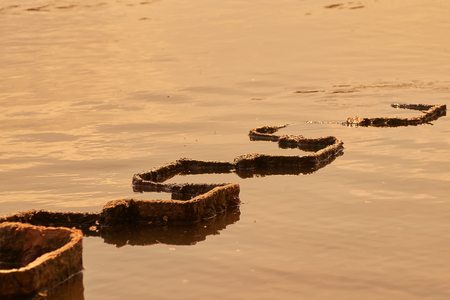 In the evening light, an angular metal structure can be seen, the snake-shaped into the water
