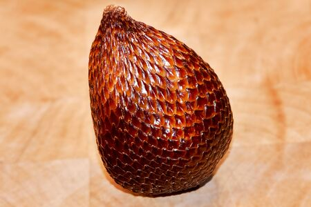 Snake fruit Salak in detail on a wooden plate. You see the fine grain and structure of the skin of this ripe fruit, which looks like a snake.
