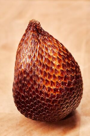 one Snake fruit Salak in detail on a wooden plate. You see the fine grain and structure of the skin of this ripe fruit, which looks like a snake. Vertical picture