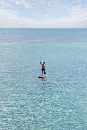 a stand up paddler SUP with blue swimming trunks on the open sea on the blue turquoise water and under a slightly cloudy sky