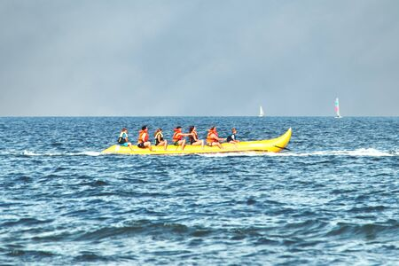 Yellow driving banana boat on the Baltic Sea on Ruegen. Sailor in the background