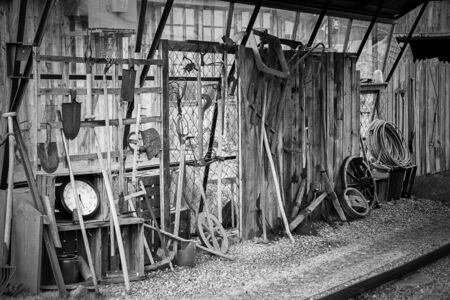 Black and white, rustic equipment and tools like shovels, pitchfork or a clock stand and hang on a wooden wall in an old shed on a farm. Stock Photo
