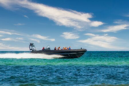 a speedboat races with people over the turquoise blue water over the waves and lets a fountain spray up behind it Foto de archivo