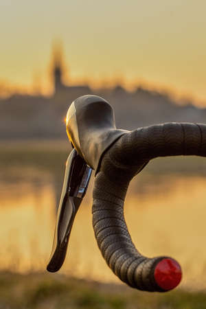 a black red racing bicycle handlebar with brake shifters against the silhouette of a city skyline of Dresden in the evening light