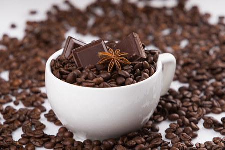 Capuccino cup filled with coffee beans, sweet chocolates and aniy star photo