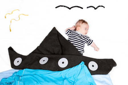 Small baby styled as sailor with ship made of blanket