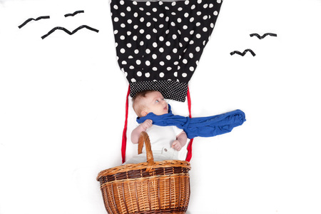 small baby styled as flying in hot-air-ballon