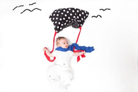 Small baby styled as flying and holding fall-breaker