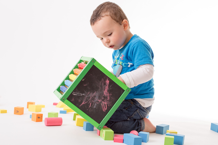 Small boy is playing with colorful cubes