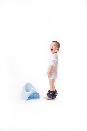 Small boy is smiling next to the blue potty