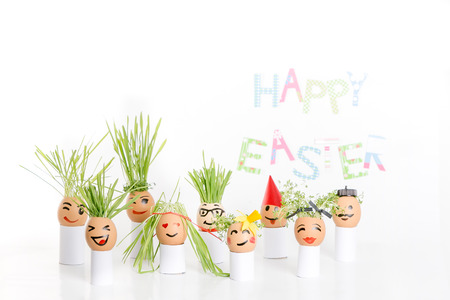 wild oats: Happy Easter decoration made of  egg-shell faces with hair Stock Photo