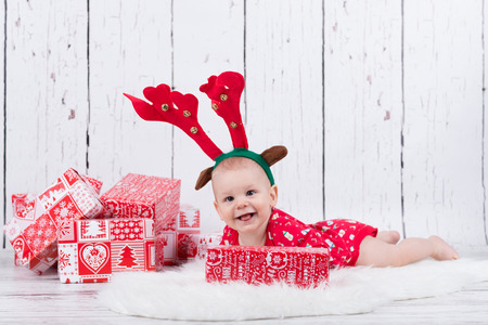 Baby as raindeer laying and smiling next to gifts Stok Fotoğraf