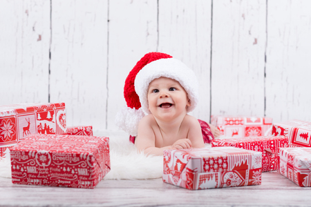 happy baby laying  among the christmas gifts Stok Fotoğraf