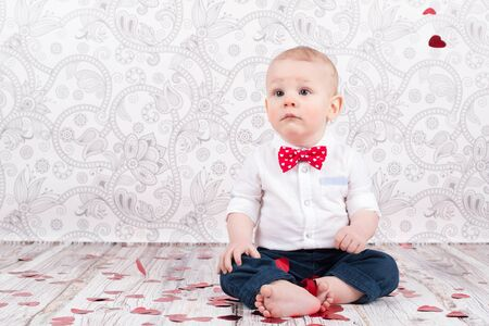 Lovely baby boy sitting among glittering red hearts Stok Fotoğraf