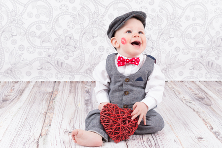 young at heart: lovely baby boy in barret with lipstick kiss on his cheek and red heart