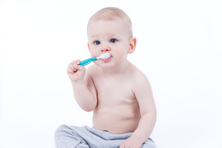 Small baby is training eating with plastic spoon Stok Fotoğraf