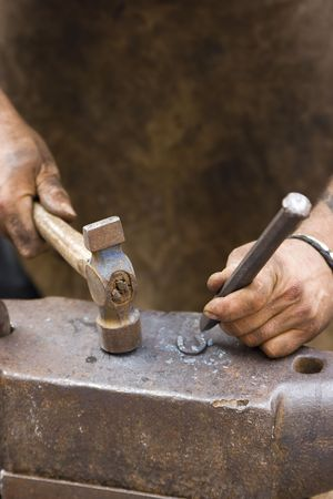 rude blacksmith striking the anvil with a hammer photo