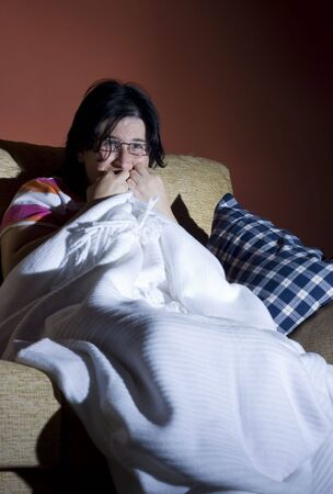 woman watching a  horror movie in the tv in a room photo