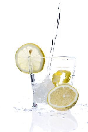 glass of liquid with lemon isolated over a withe background photo