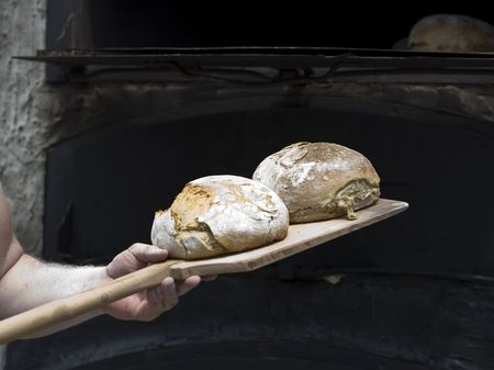 bakery oven: traditional baker making bread with an old technic Stock Photo