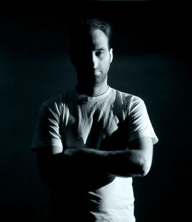 dark image of a no shaved dangerous looking guy in a rude pose photo