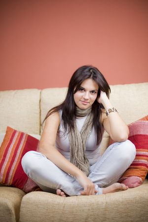 gorgeus: beautiful girl portrait sitting in the sofa of a living room