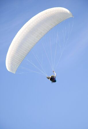 parapente: extreme active paraglider flyng over a blue sky