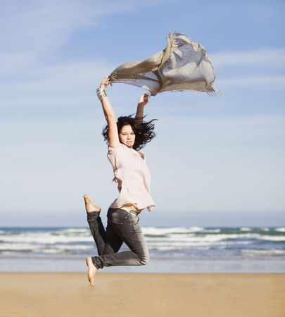 beautiful happy young girl running and jumping over a windy beach with a blowing scarf Stock Photo - 6187226