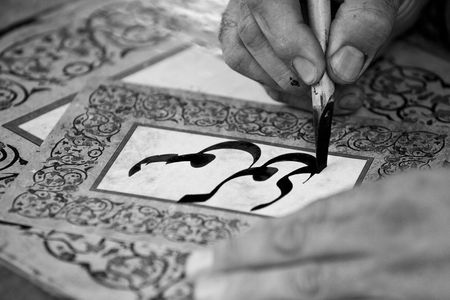 a man writing a name with traditional arab characters in a beautiful card Stock Photo