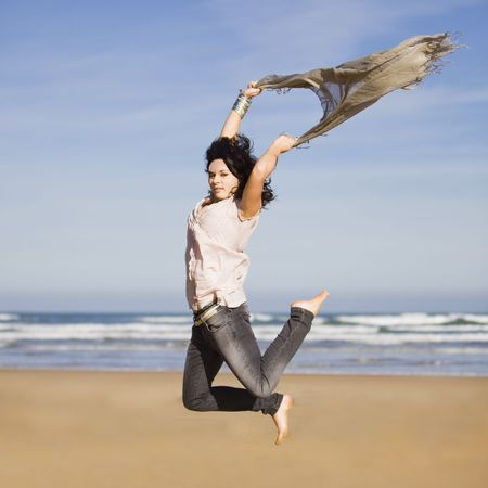 beautiful happy young girl running and jumping over a windy beach with a blowing scarf photo