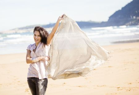 a young pretty girl with a scarf in a beach in a sunny beach  photo