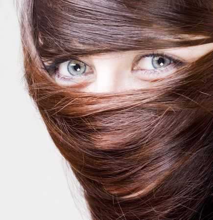 extrange look of a young woman with blue eyes with her hair around the eyes photo