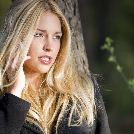 una bella ragazza reale parlando con il suo cellulare nella natura