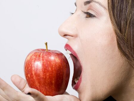 a young pretty girl eating a fresh healthy red apple photo