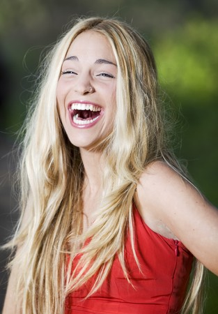 beautiful girl with a red dress in the nature laughing