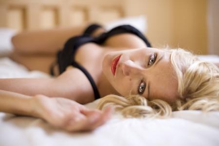 sexy donna bionda con gli occhi blu stupefacente posa sul letto  Archivio Fotografico