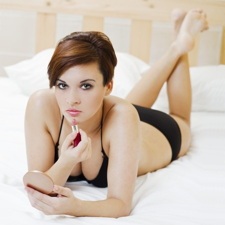 sexy young brunette girl on the bed applying herself a lipstick photo