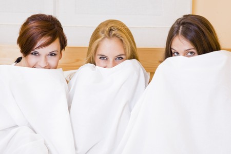three young beautiful sexy friends playing in the bed Stock Photo - 7419292