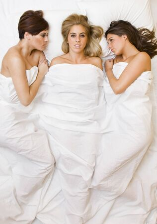 three young beautiful sexy friends playing in the bed photo