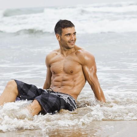 sexy indoeuropea adatta uomo posa in una spiaggia  Archivio Fotografico